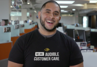 A smiling Raphael stands in Audible Customer Care center wearing a customer care shirt.