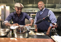 Chef Marcus Samuelsson at the stove of one of his restaurants with a guest standing by him smiling.