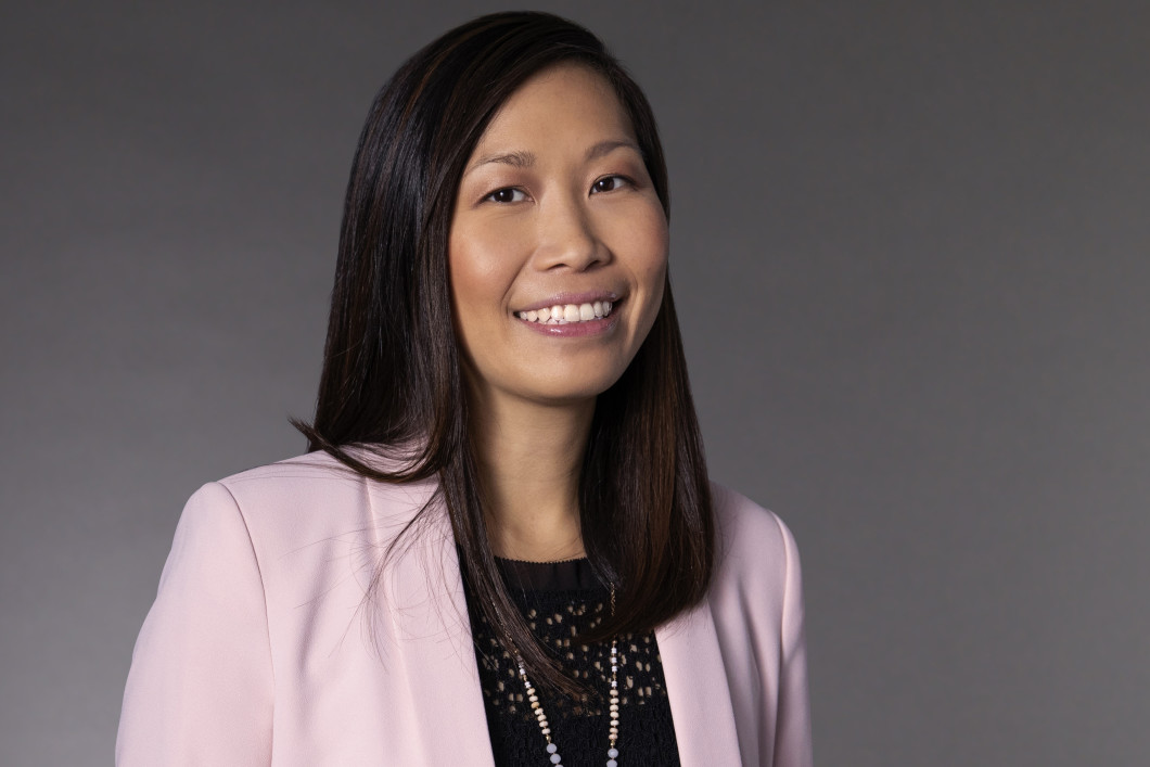 Audible's CFO Cynthia Chu stands against a grey background in a black eyelet shirt and pink blazer.