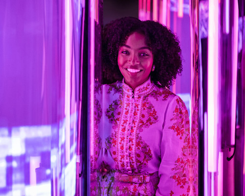 Yara Shahidi stands in a brightly lit purple room.