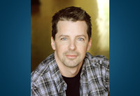 Actor Sean Hayes, seated, stares into the camera.