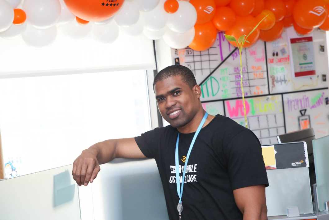 Sanchez Brown smiles directly at the camera with one arm leaning up on his desk at the Audible headquarters in Newark. Orange and white balloons with Audible logos displayed surround him.