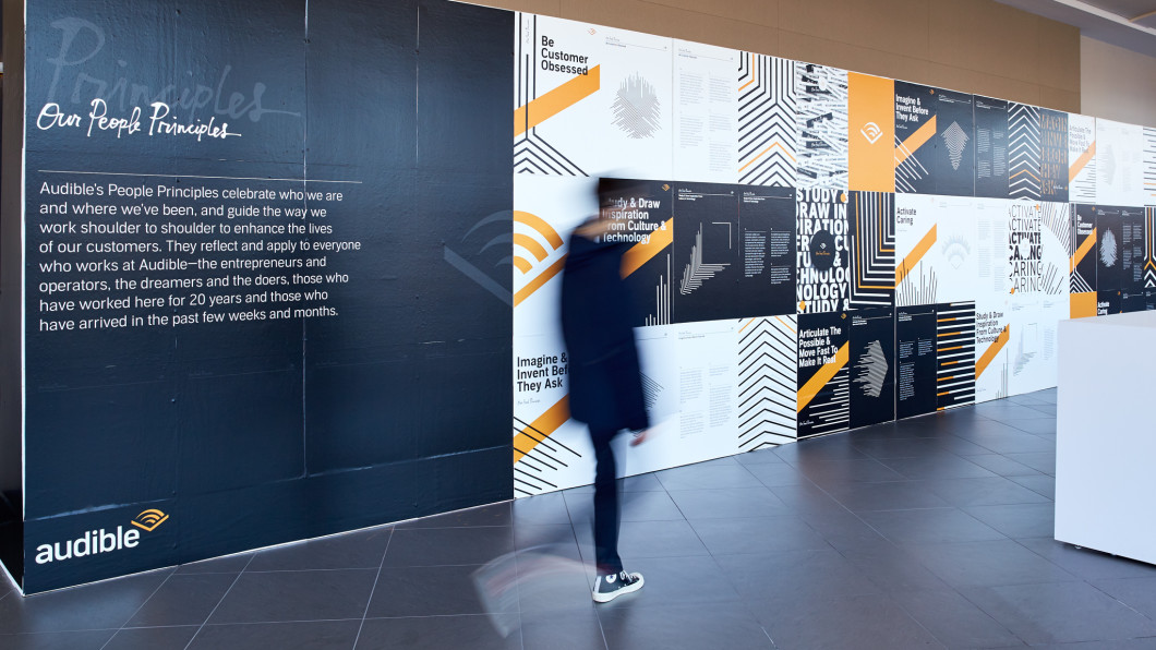 An employee dressed in all black is walking past a wall in our lobby that outlines all of our people principles and our new design featuring lines in various patterns for each of our principles.