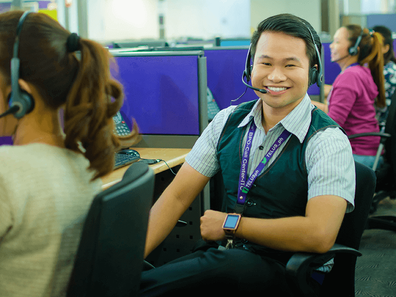 TELUS International team member sitting in the call center