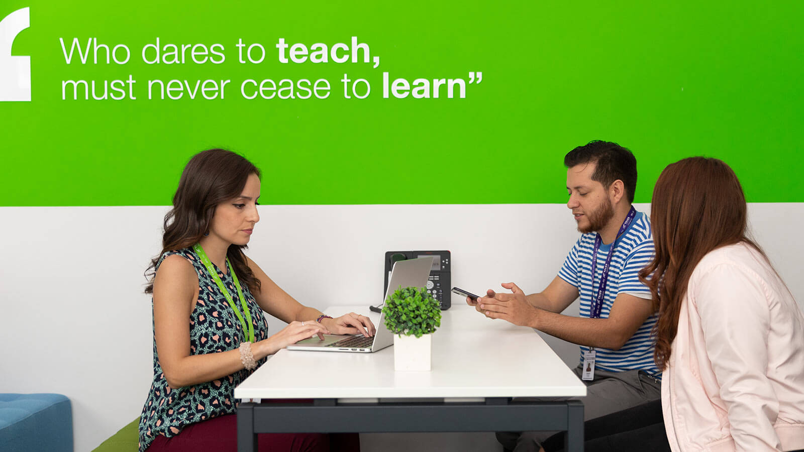 "Group of people working on a desk by a wall with a quote: ""Who dares to teach must never cease to learn"""