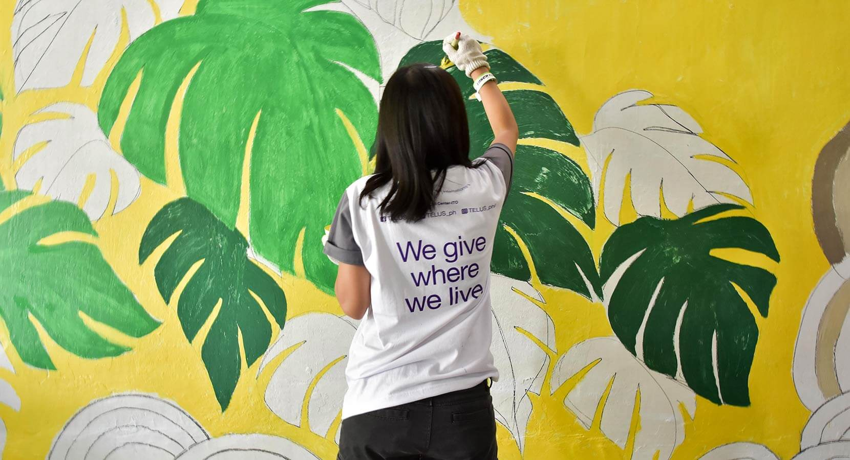 "A woman wearing a ""We give where we live"" shirt painting a leaf wall mural"