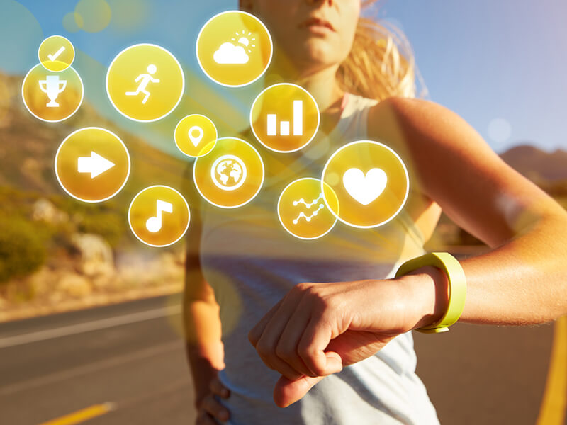 woman wearing IoT-enabled watch with multiple health icons indicated
