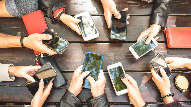 Group of people with their mobile phones out around a table