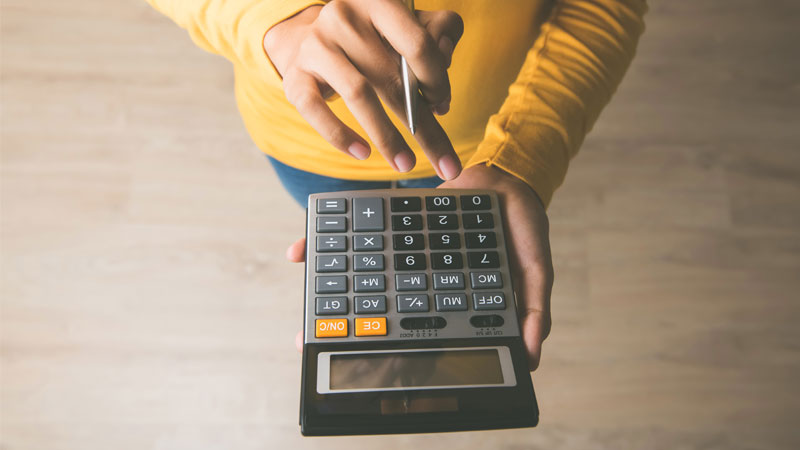 woman determining cost on calculator