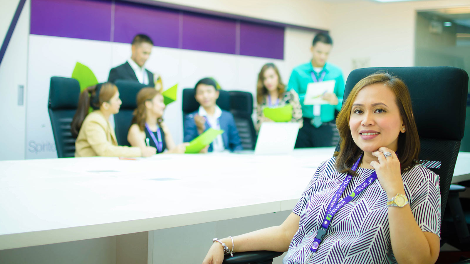 Woman sitting a meeting room desk with her team members in the background