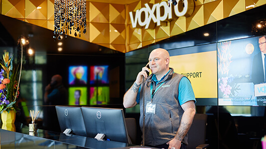 Man standing and talking on phone at a desk in front of a wall that says 'voxpro'