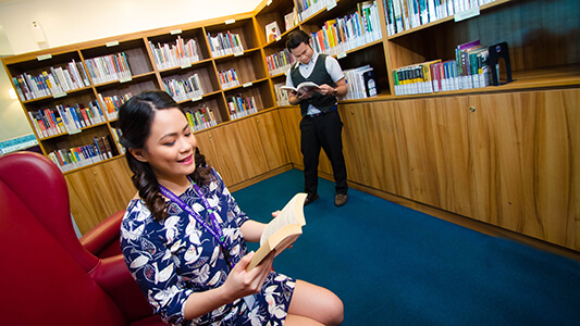 A man and a woman reading a book in an office library