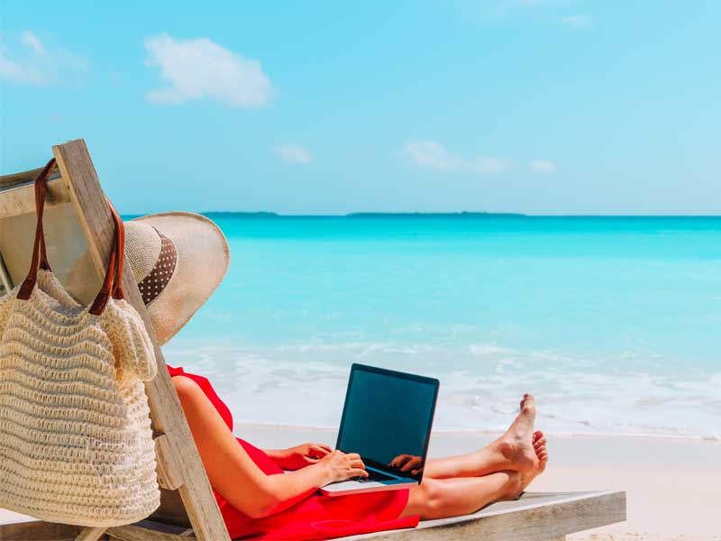 woman sitting on beach with laptop