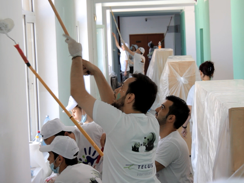 Team members demonstrating corporate social responsibility by painting walls in a children's center