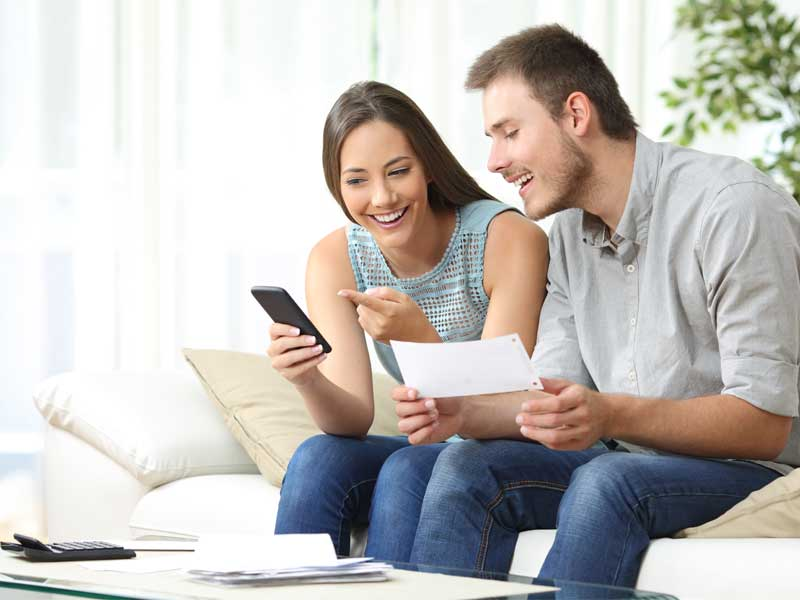 Millennial couple looking at banking information on phone