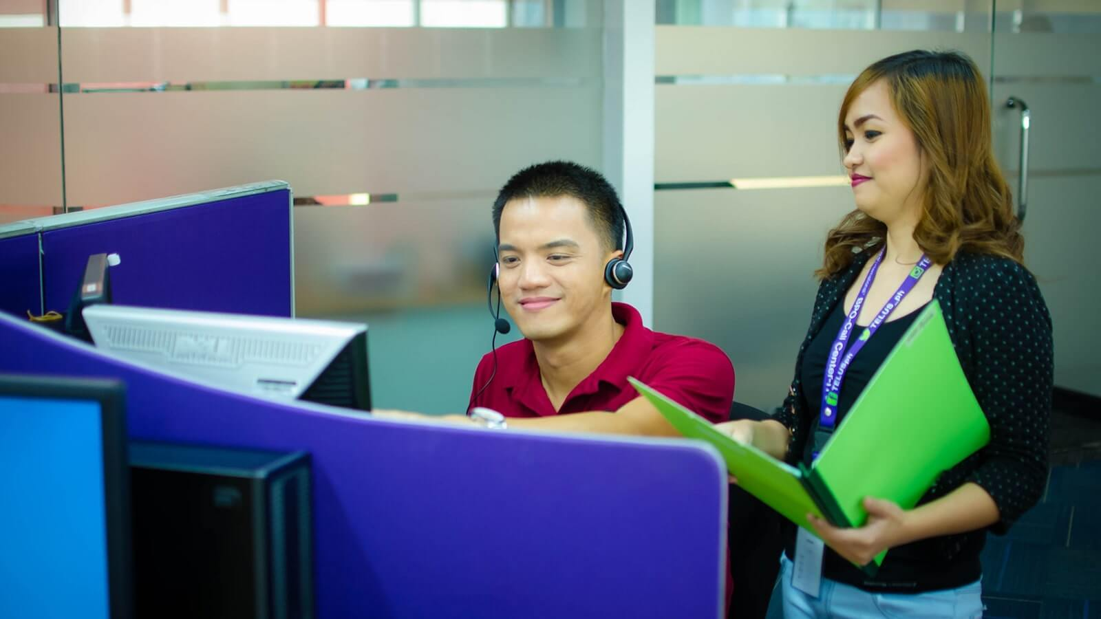 A call center employee showing something on his screen to his boss