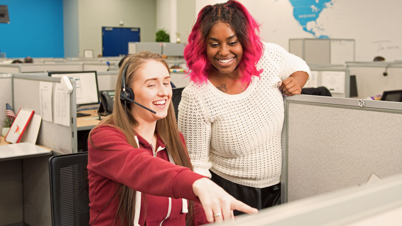 Two female TELUS International team members in the call center