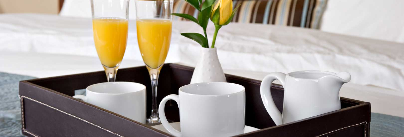 Drinks tray with coffee, orange juice and a flower center piece