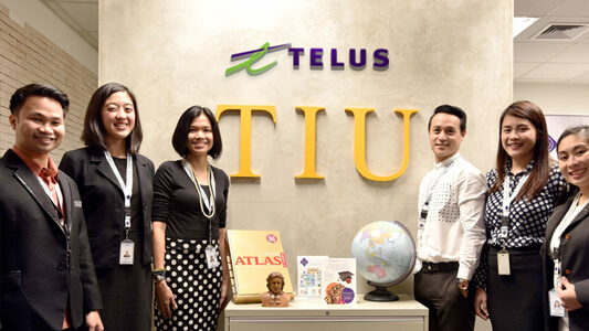 Six people standing in front of a wall that says TELUS TIU and a table with an atlas and a globe