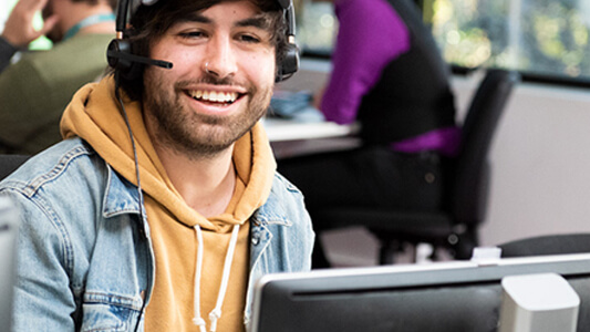 Male call centre employee wearing a microphone headset smiling in front of a computer
