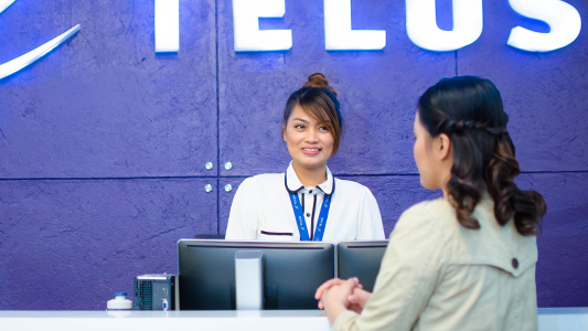 Two women having a conversation at a TELUS international office space in the Philippines