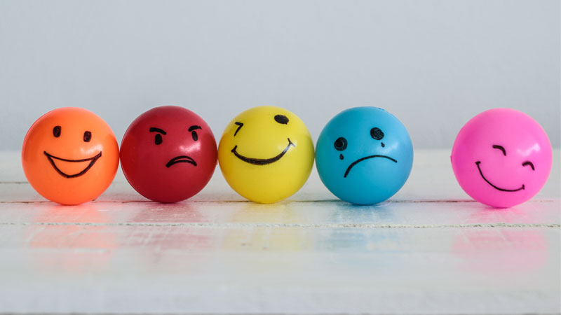 Set of colorful balls with faces drawn on representing different customer emotions.