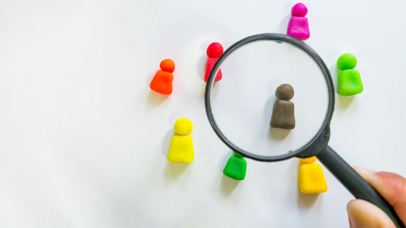 magnifying glass looking at colorful clay figures representing people to hire