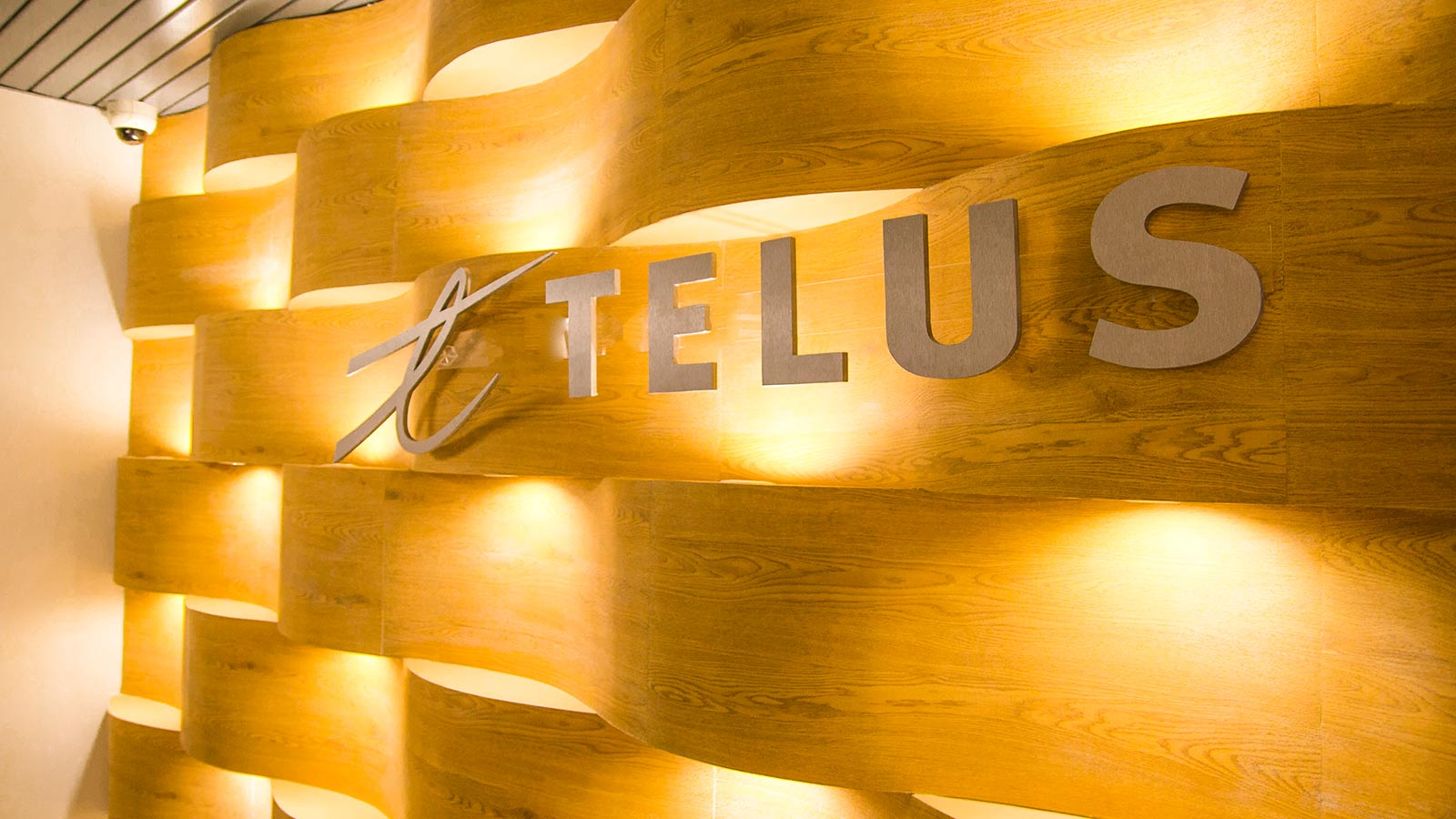 TELUS logo on a wood wall