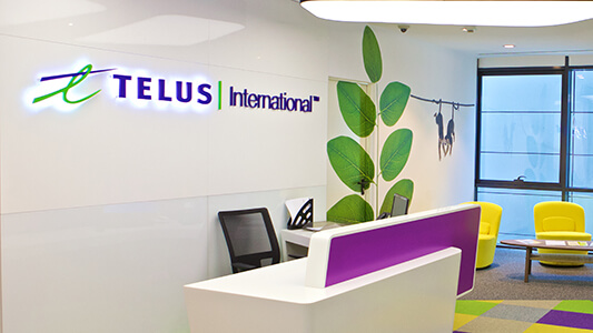 Desk in front of wall with TELUS International and a branch of a plant on it