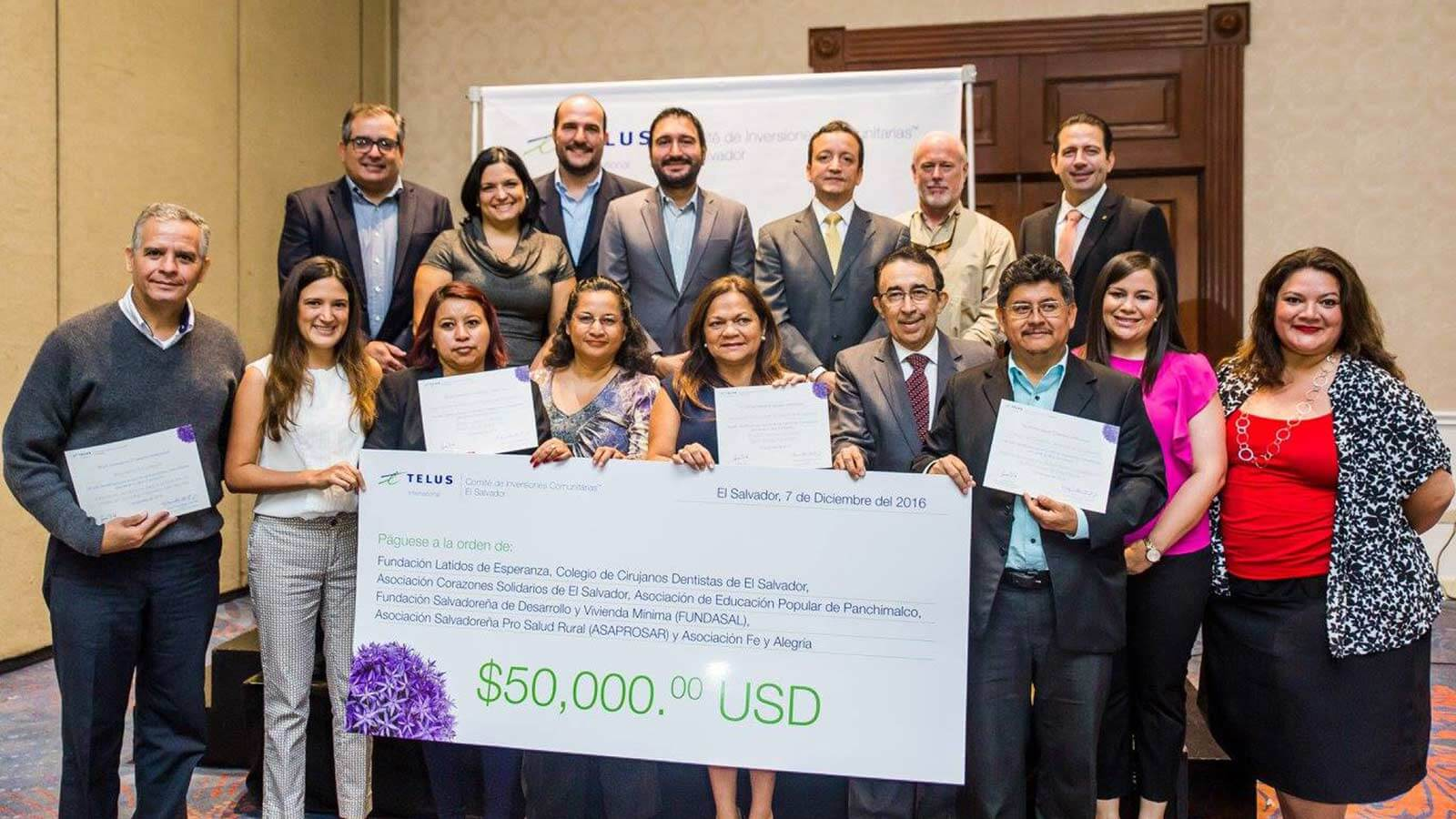 A group of people smiling and holding a large $50,000 USD cheque