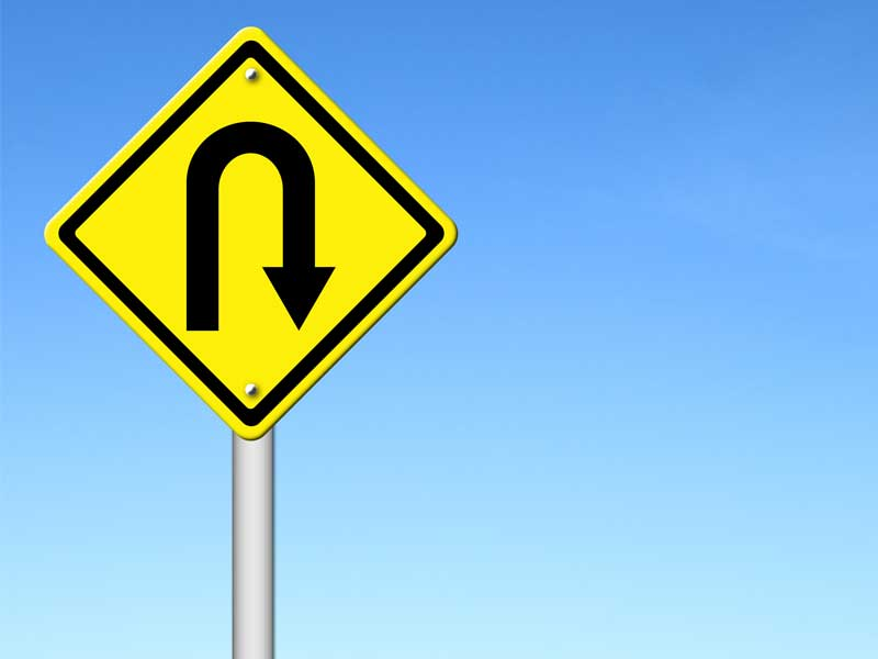 Yellow u turn sign on blue background