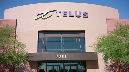 The front entrance of a building that says TELUS and then 2251 over the door