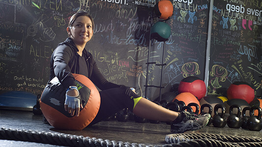 A woman at the gym holding a weighted ball