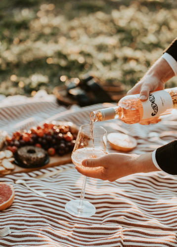 Pouring rosé wine on a picnic