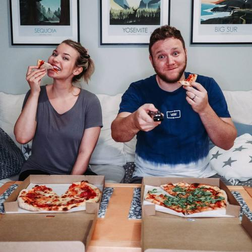 Man and woman eating pizza and watching TV. Photos for Wolt's marketing.