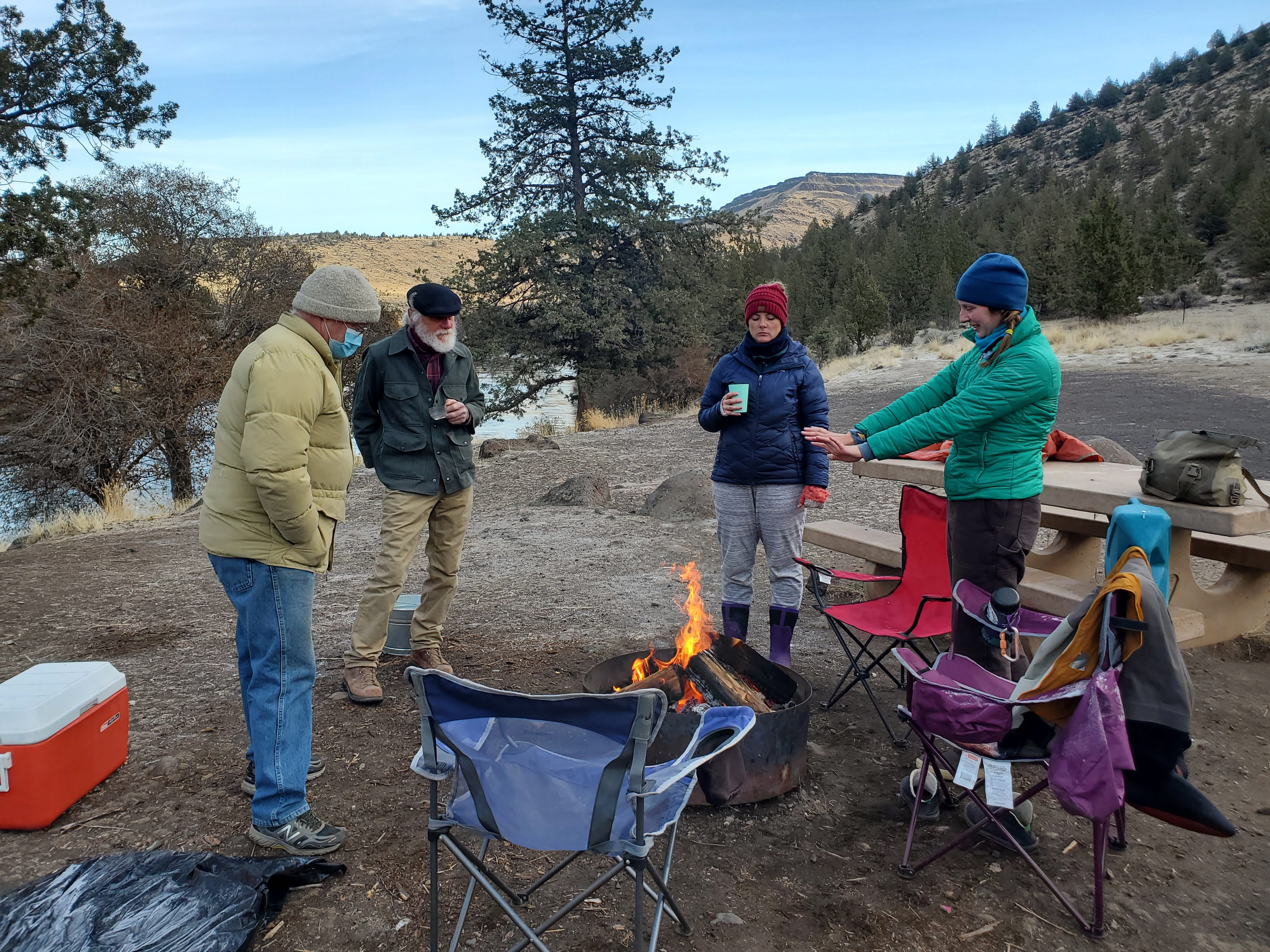 The project team warms up by a fire at their campsite before starting a long (and chilly) day of sampling.