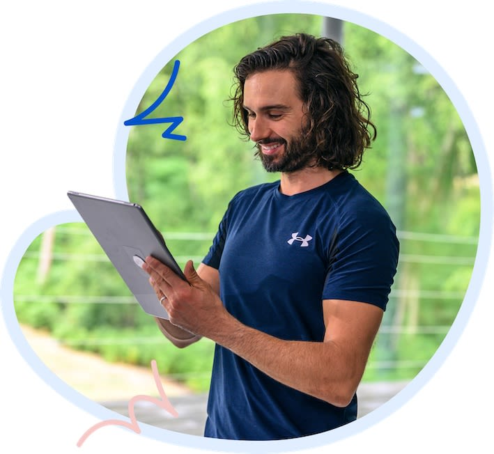 Joe Wicks reviewing a plan on his tablet