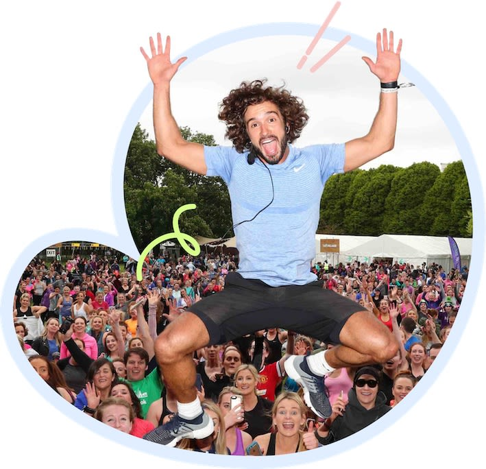 Joe Wicks jumping enthusiastically in front of a crowd