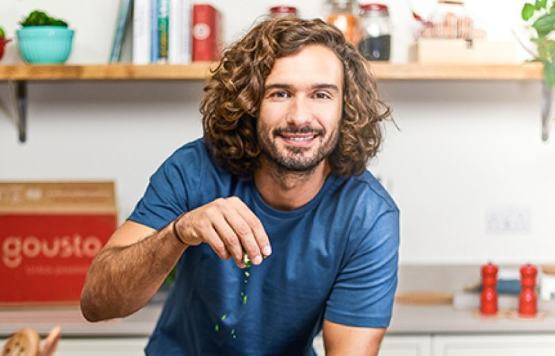 Joe Wicks adding garnishing with a Gousto recipe box behind him