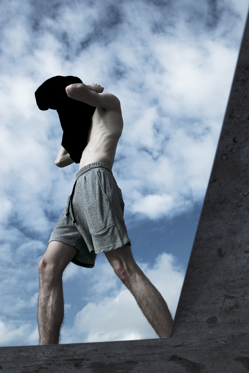 Man with gym shorts and shirt over head