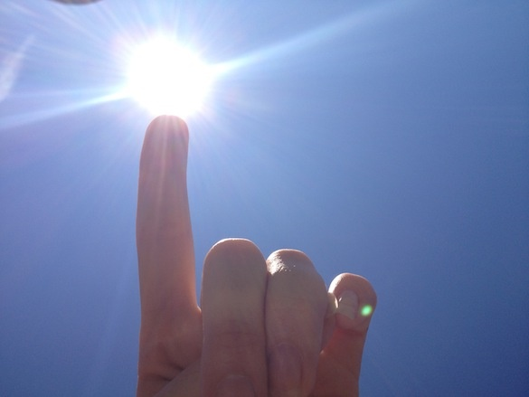 Finger pointing into the sun