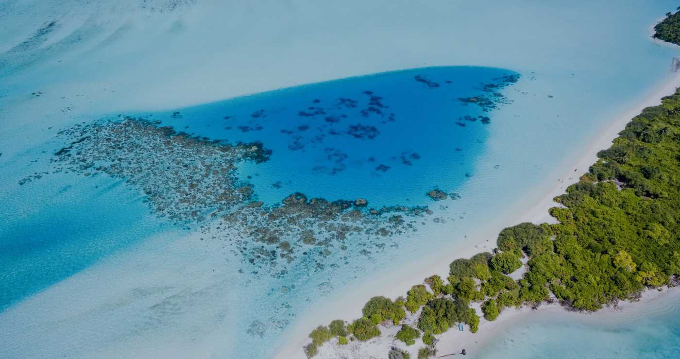 Aerial view of an island with a turquoise water sea on the background