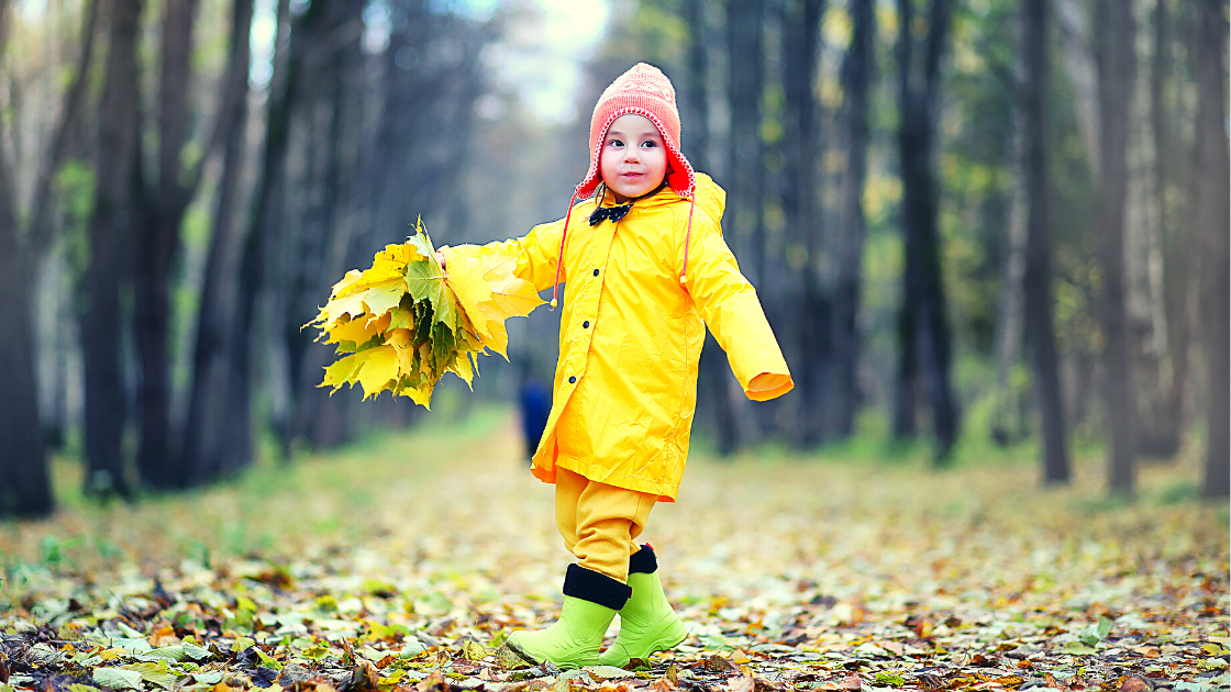 Toddler in yellow raincoat with orange beanie and green boots walking through the forest during Autumn