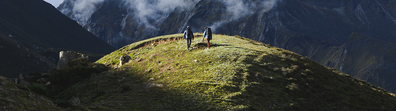 two people trekking on a mountain