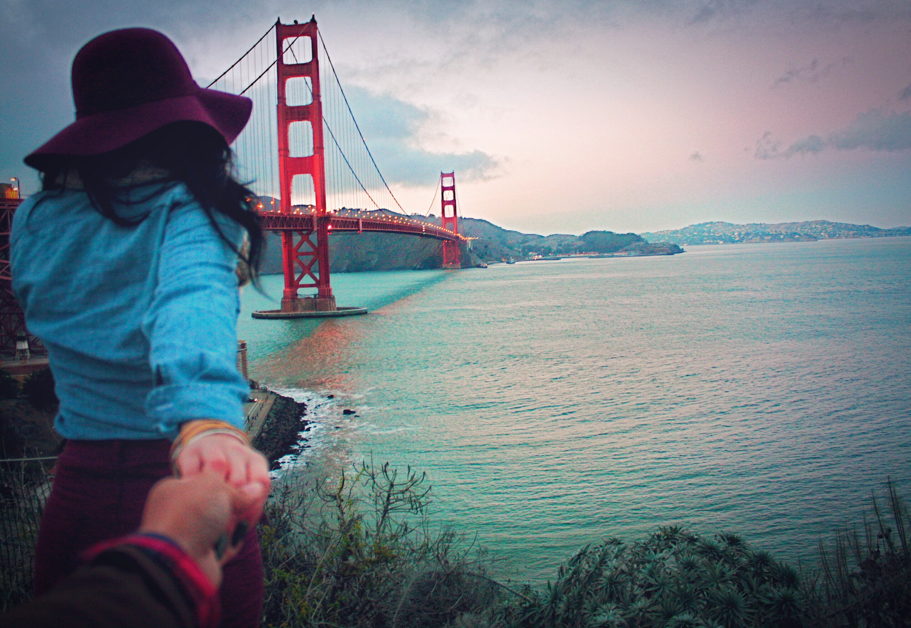 couple holding hands by the golden gate bridge