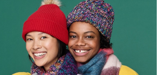 two women smiling in toques