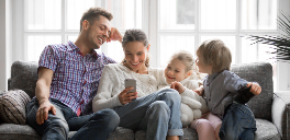 Family sitting on sofa looking at mobile phone