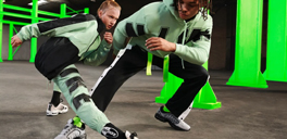 a man and boy in a low pose with green nikes