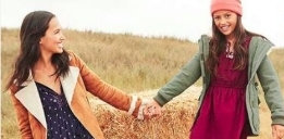 two friends holding hands in a field