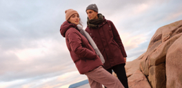 a man and woman wearing maroon jackets and toques standing with a sunset in background